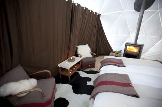 Chambre de l'hotel Whitepod avec cheminée