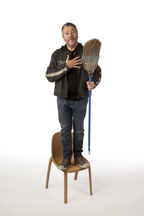 Philippe Starck debout sur sa Broom chair