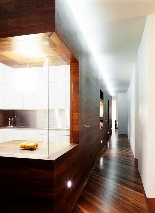 La cuisine avec des murs couverts de bois et une vitrine