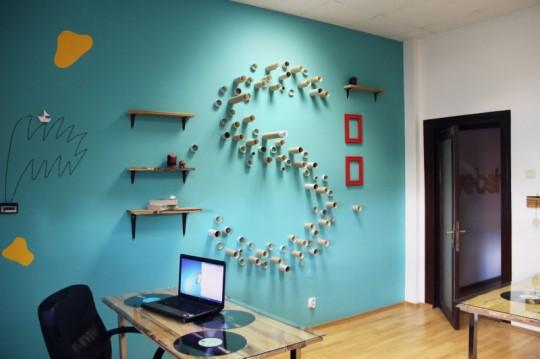 Bureaux Webshake - un S dessiné avec des morceaux de tuyaux sur le mur