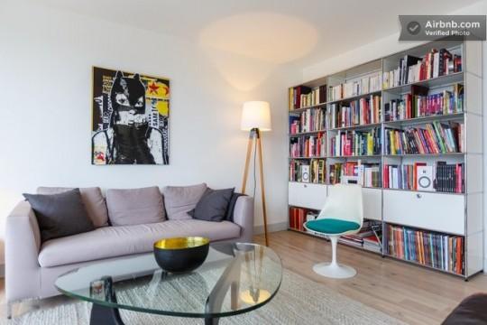 Salon avec un canapé gris, un tableau BD et une grande bibliothèque