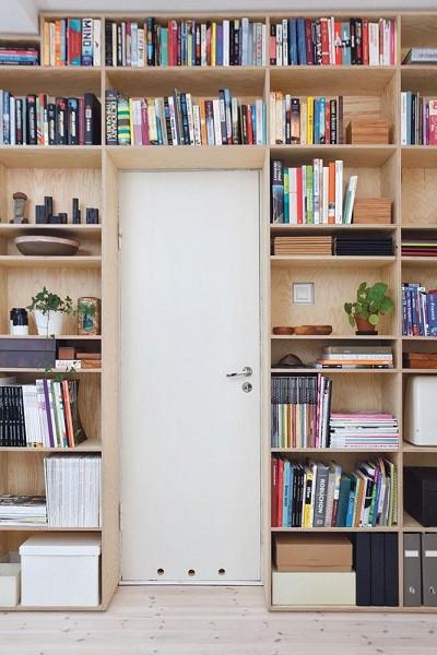 Bibliothèque aménagée autour de la porte d'un appartement