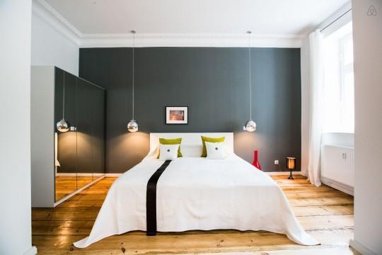 Chambre avec un mur gris et un parquet massif