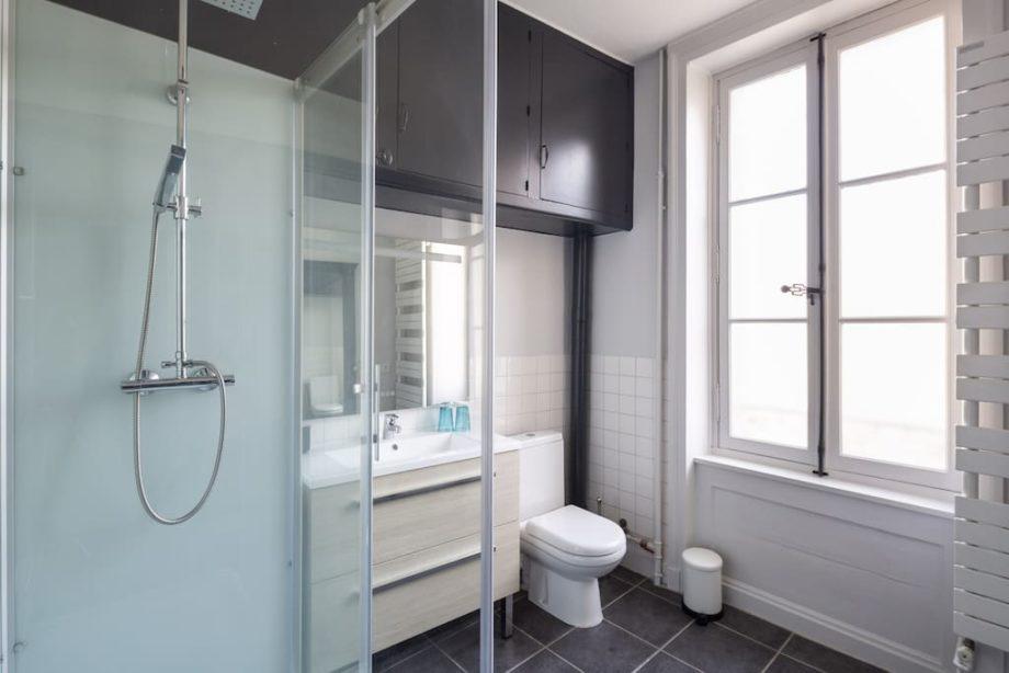 Salle de bain avec cabine de douche moderne et miroir avec éclairage tactile