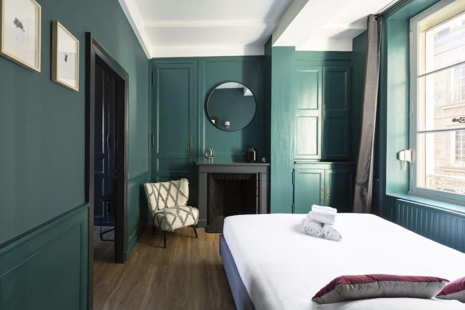 Chambre avec une cheminée et un miroir rond